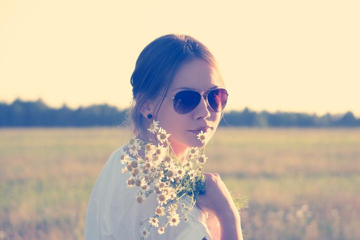 Lady wearing sun glasses standing in a field holding flowers.