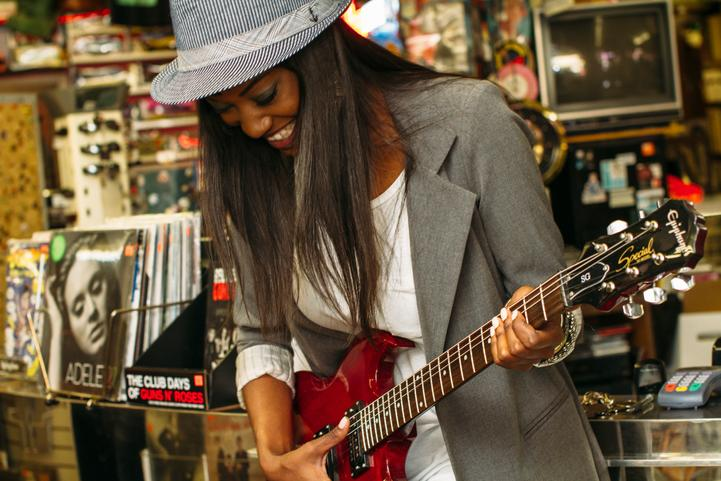 Young woman in music store holding a guitar..