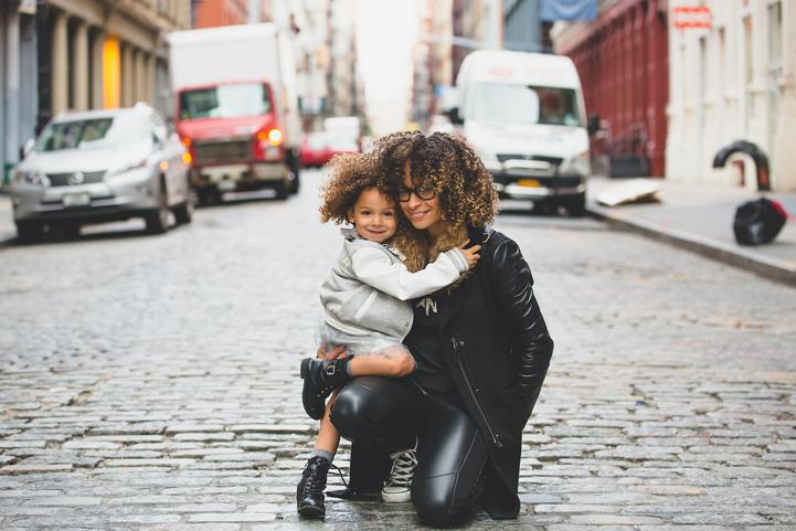 Mother and daughter hugging on a cobblestone street.